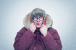 Frozen man in glasses and winter clothes warming ears, cold, snow, blizzard