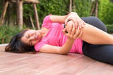 Asian woman runner touching her injured knee at outdoor - pain concept. - 176122911