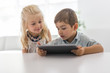 Adorable brother and sister young child using tablet