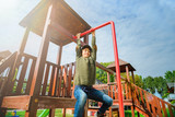 curious fearless little girl climbing on playground alone in sunny weather - 176134368