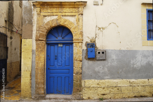 Fotobehang Marokko Blue wooden door on the street of medina