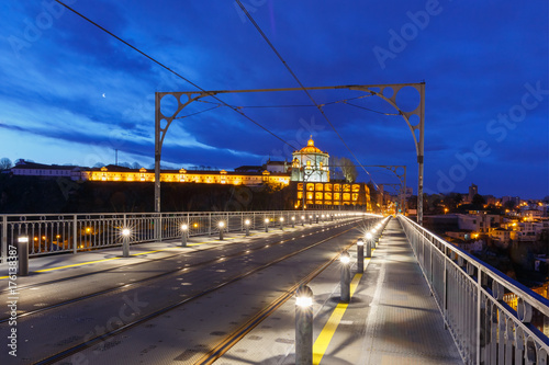 Foto op Plexiglas Donkerblauw Empty tram rails on the Dom Luis I or Luiz I iron arch bridge across Douro river and Monastery of Serra of Pilar in Porto during morning blue hour, Portugal.