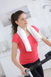 sporty woman training on exercise bike in the living room