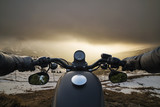 handlebars of a motorcycle in the foreground in front of a sunset in the mountains
