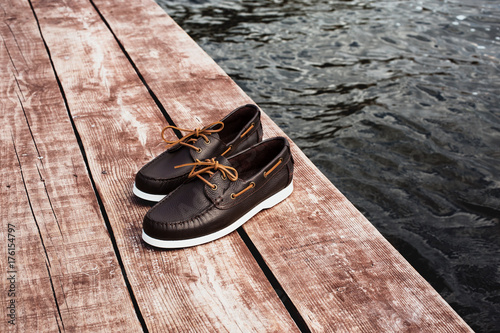 Aluminium Zeilen Brown leather men's top sider shoes or boat shoes with white sole on a brown wooden pier or on a brown wooden boards near the water, or rivers, or lakes, or the sea. Fashion advertising shoes photos.