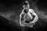 Awesome power athletic man bodybuilder screaming while flexing his muscles. Fitness muscular body on dark smoke background. Perfect male. - 176155789