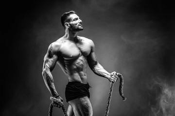 Side view of muscular bodybuilder man training hard with rope in studio, smoke. © zamuruev