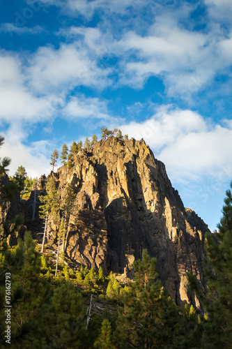 Tuinposter Zwart Rocky Peak Stands Tall in Cloudy Sky