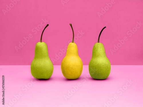 Fotobehang Pop Art Pears Pop art Two green and one yellow pears are standing upright in a row on pink background Trendy still life with fruits