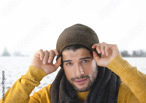 Man wearing hat and scarf in snow landscape