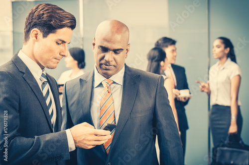 Mixed Asian and Caucasian business team meeting on terrace on front of their office