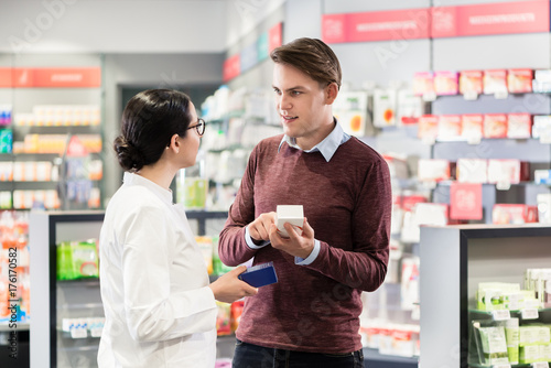 Experienced female pharmacist checking the indications and contraindications of a new medicine next to a young male customer in a modern pharmacy - 176170582