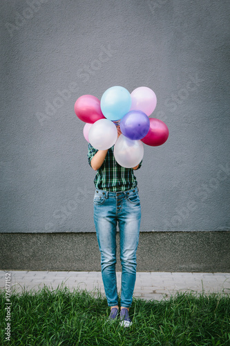 Young woman hiding behind colorful air balloons