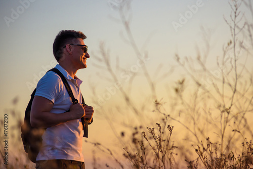 Happy and carefree man standing on a country road close to the wild steppe field. Freedom and love to nature concept. Male adult traveler observes the sunset with optimism and confidence. © vladhhe