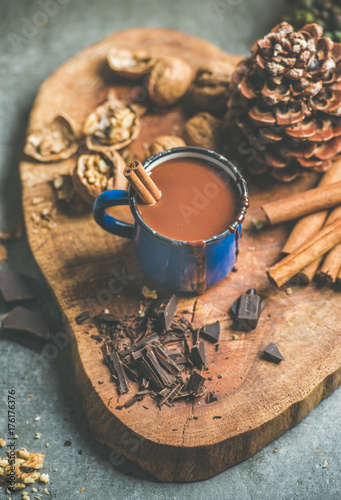 Fotobehang Chocolade Rich winter hot chocolate with cinnamon and walnuts in blue enamel mug on wooden board over grey concrete background, selective focus