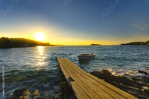 Small Boat and Wooden Pier at sunset