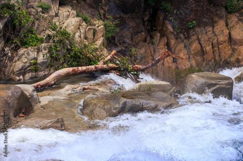 Fotobehang Bergrivier Foamy River Flow against Brown Stones