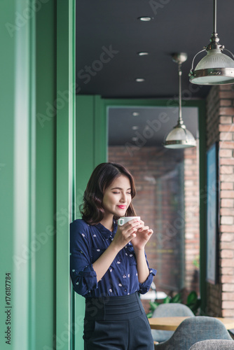 Wall mural Portrait of happy young business woman with mug in hands drinking coffee in the morning at restaurant
