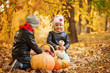 Kids playing in in autumn park with pumpkins and apple.