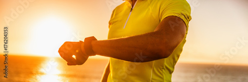 Fotobehang Hoogte schaal Smartwatch biking cyclist athlete using smart watch activity tracker gps during cycling training. Road bike sports man using his watch app for fitness tracking. Panoramic crop.