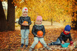 Three happy friends kids in autumn park with small pumpkins.