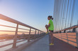 Man stretching after jogging / exercise on a bridge.