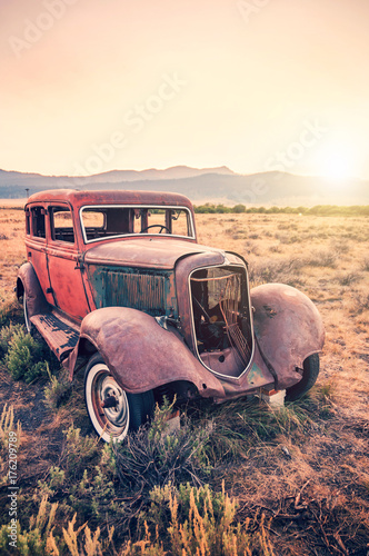 Poster Old rusty antique car, abandoned in a field at sunset