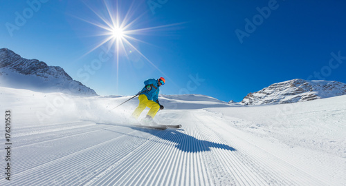 Young man skier running down the slope in Alpine mountains