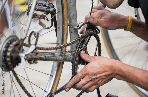 In de dag Fiets Mechanic fix the chain of a vintage bicycle