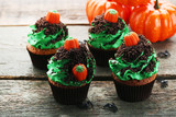 Halloween cupcakes on wooden table - 176218334