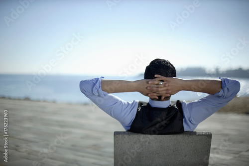 Business man sitting by shoreline