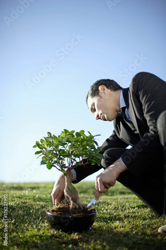 Business man nurturing bonsai outdoors Poster