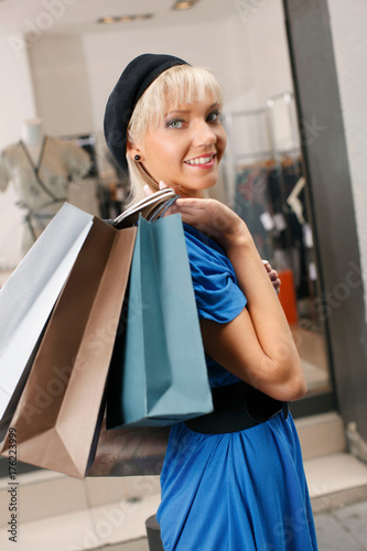 Plakát Young woman walking with shopping bags