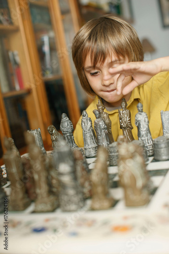Young boy playing chess Poster