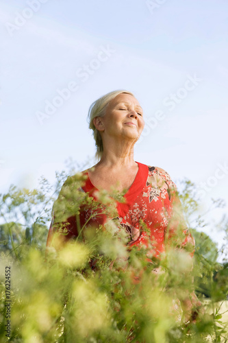 Portrait of mature woman with flowers Poster