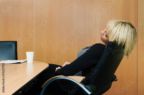 Woman relaxing in boardroom Poster