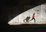Powerful athlete sprinting and running. Man training and casting shadow in a wall. - 176229335