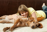 Young woman cuddling with her dog