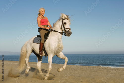 Woman riding horse on the beach