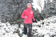 Winter running in park: happy active woman runner jogging in snow, outdoor sport and fitness concept