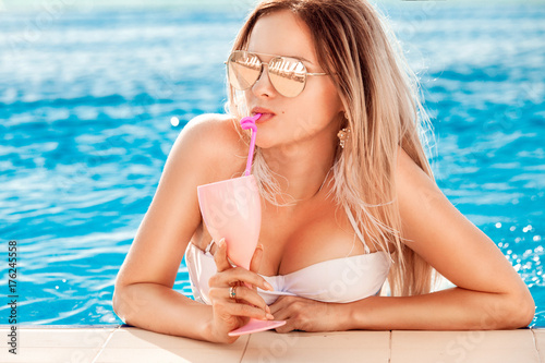 Fotobehang Spa Summer Vacation. Woman in bikini on the inflatable donut mattress in the SPA swimming pool with coctail.