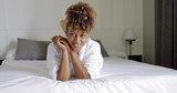 Portrait of young wonderful woman with curly hair wearing white bathrobe and lying on bed in hotel posing playfully and looking at camera. - 176248709
