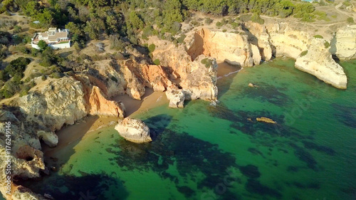 Fridge magnet Shot taken with drone of green water washing sandy and rocky beach of coastline with house placed on hill above in bright sunlight, Portugal, Algarve.