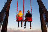Young couple on the swing on the roof of tower at sunset time - 176251305