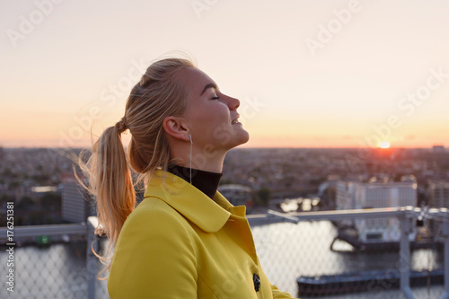 Woman admires the urban landscape at sunset