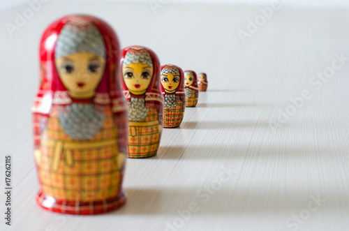Five red matryoshka. Long shadows. Selective focus