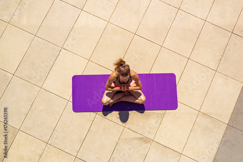Sticker Young woman in lotus position in sunny day, outdoor, view from above.