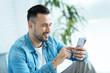 Positive minded gentleman using smartphone indoors