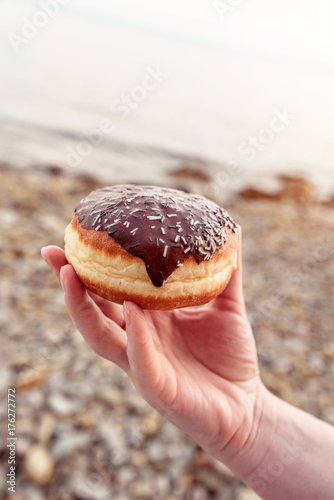 Female hand holding chocolate donut at seaside beach Poster