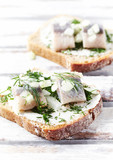 Canapes with cream cheese, salted herring and herbs - 176274322